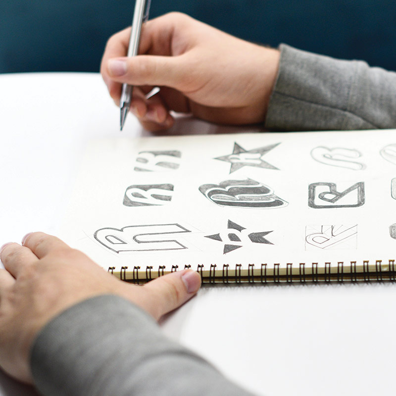 hands drawing logos on sketch book